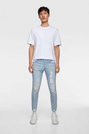 Zara Spodnie jeansowe rurki z rozdarciami przy mankietach nogawek